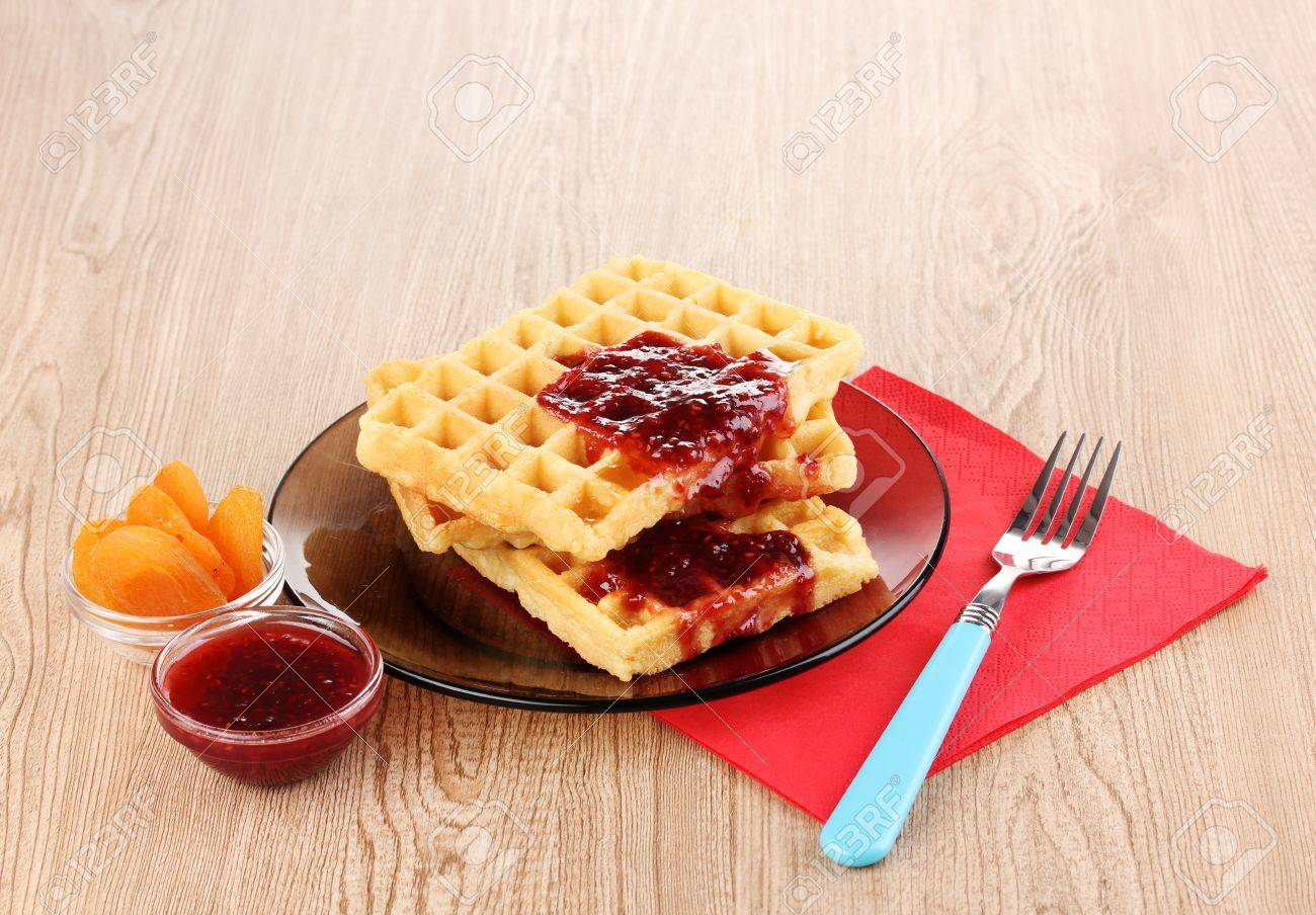 Tasty waffles with jam on plate on wooden background Stock Photo - 12330123