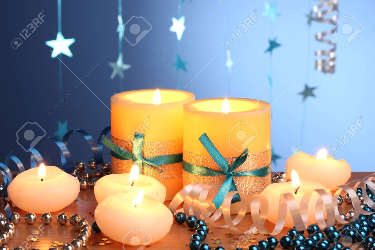 Beautiful candles, gifts and decor on wooden table on blue background Stock Photo - 12330085