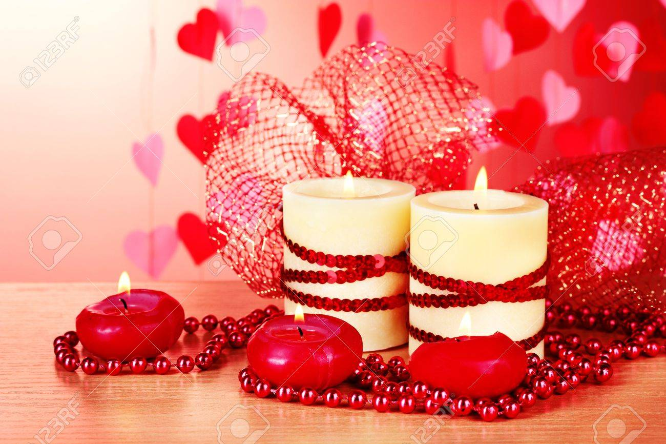 Beautiful candles with romantic decor on a wooden table on a red background Stock Photo - 12431173