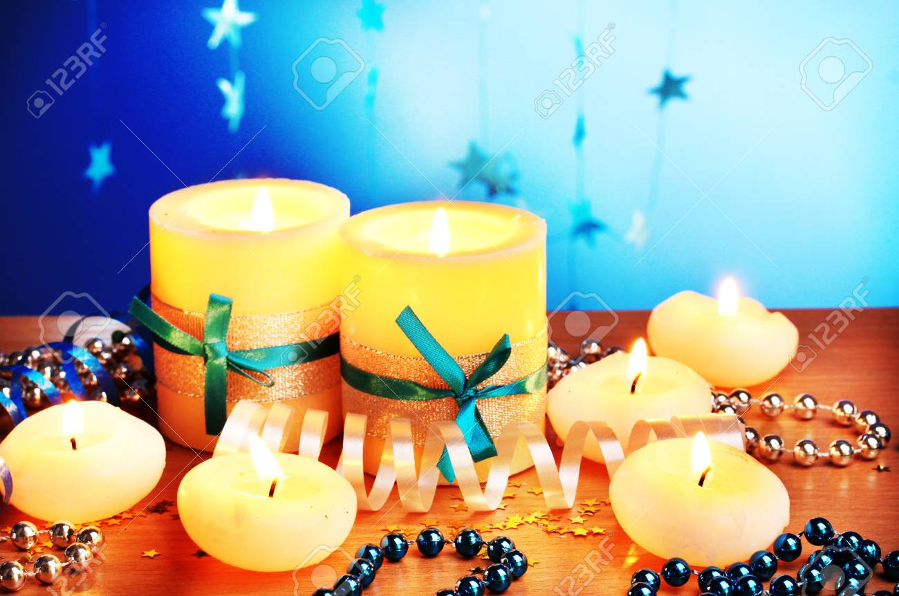 Beautiful candles, gifts and decor on wooden table on blue background Stock Photo - 12431183