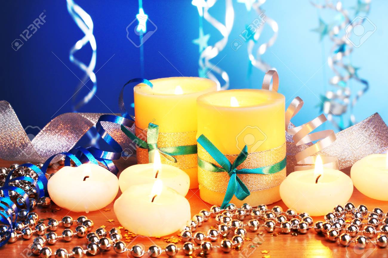 Beautiful candles, gifts and decor on wooden table on blue background Stock Photo - 12430949