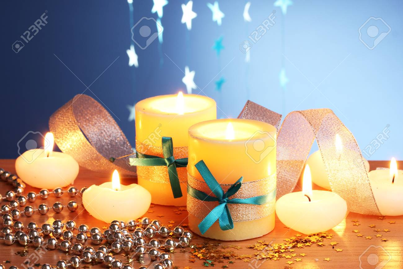 Beautiful candles, gifts and decor on wooden table on blue background Stock Photo - 12546215