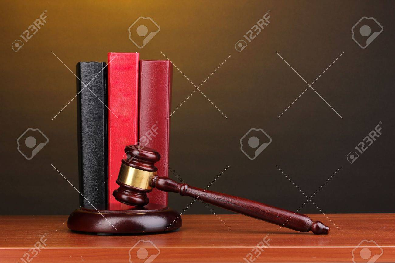 Judge's gavel and books on wooden table on brown background Stock Photo - 12553118