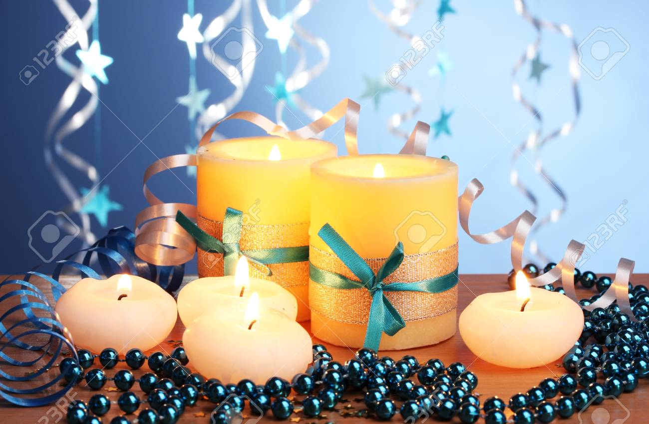Beautiful candles, gifts and decor on wooden table on blue background Stock Photo - 12715770