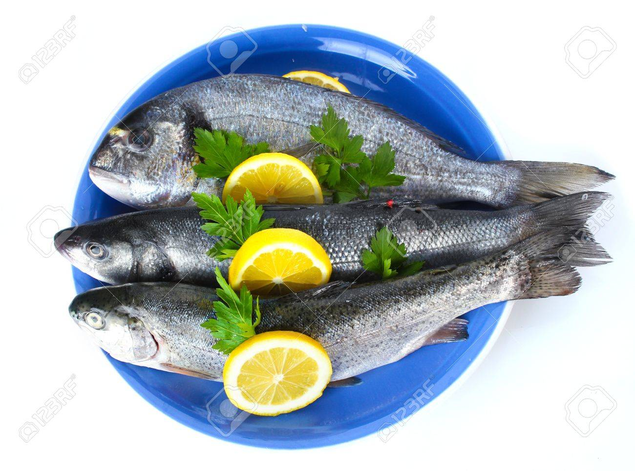 Fresh fishes with lemon and parsley on plate isolated on white Stock Photo - 13061754