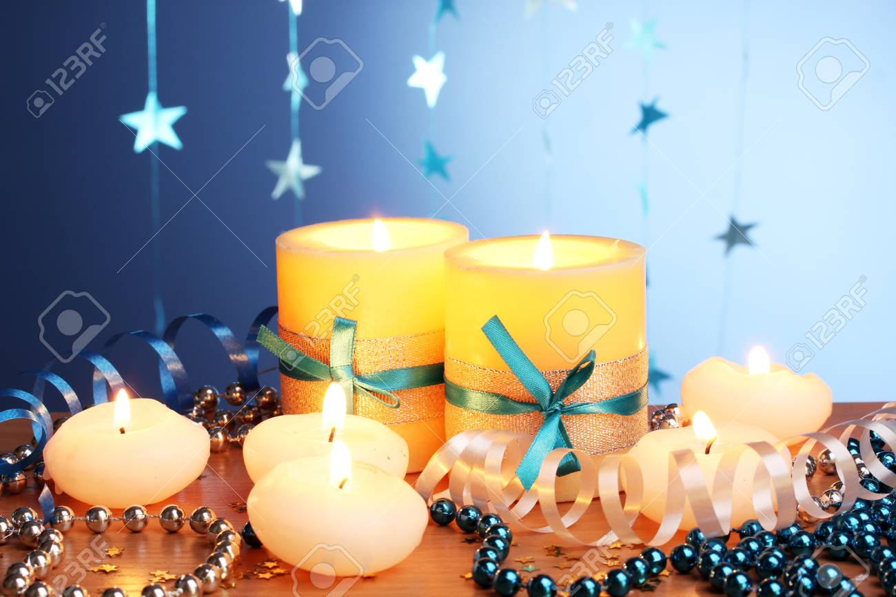 Beautiful candles, gifts and decor on wooden table on blue background Stock Photo - 13129036