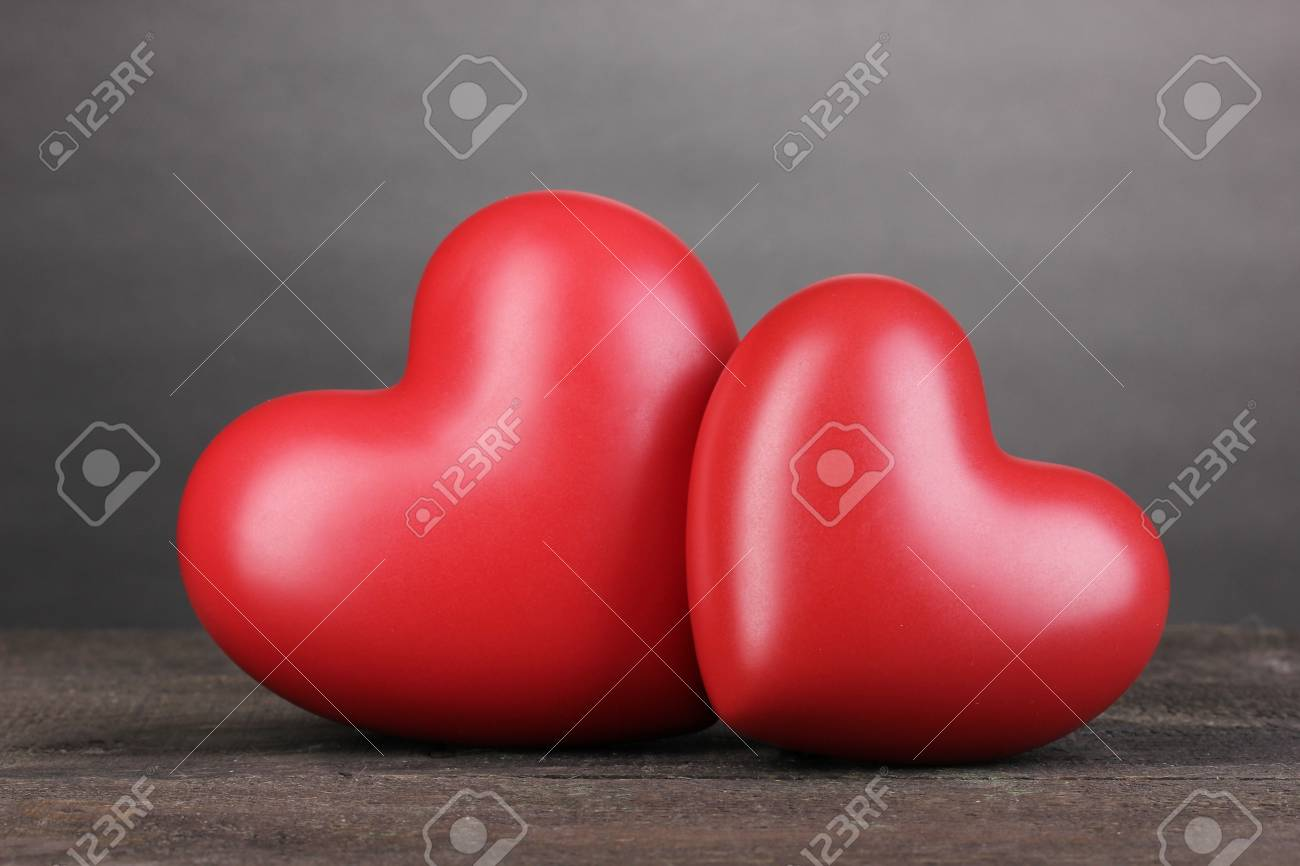 Two decorative red hearts on wooden table on grey background Stock Photo - 13163803