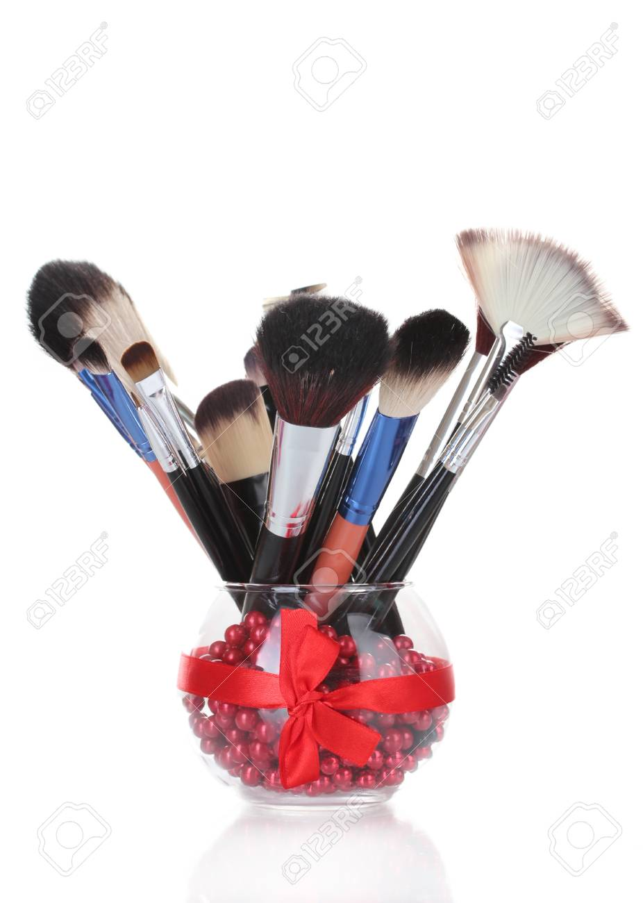 make-up brushes in glass vase isolated on white Stock Photo - 13234383