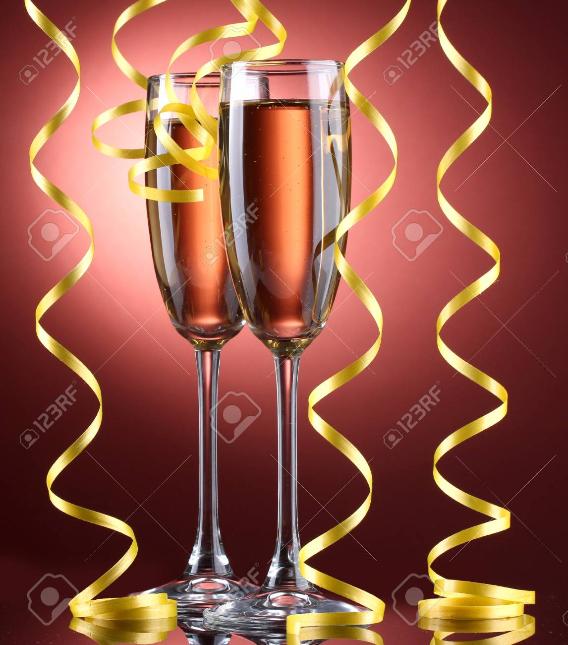 glasses of champagne and streamer on red background Stock Photo - 13275545