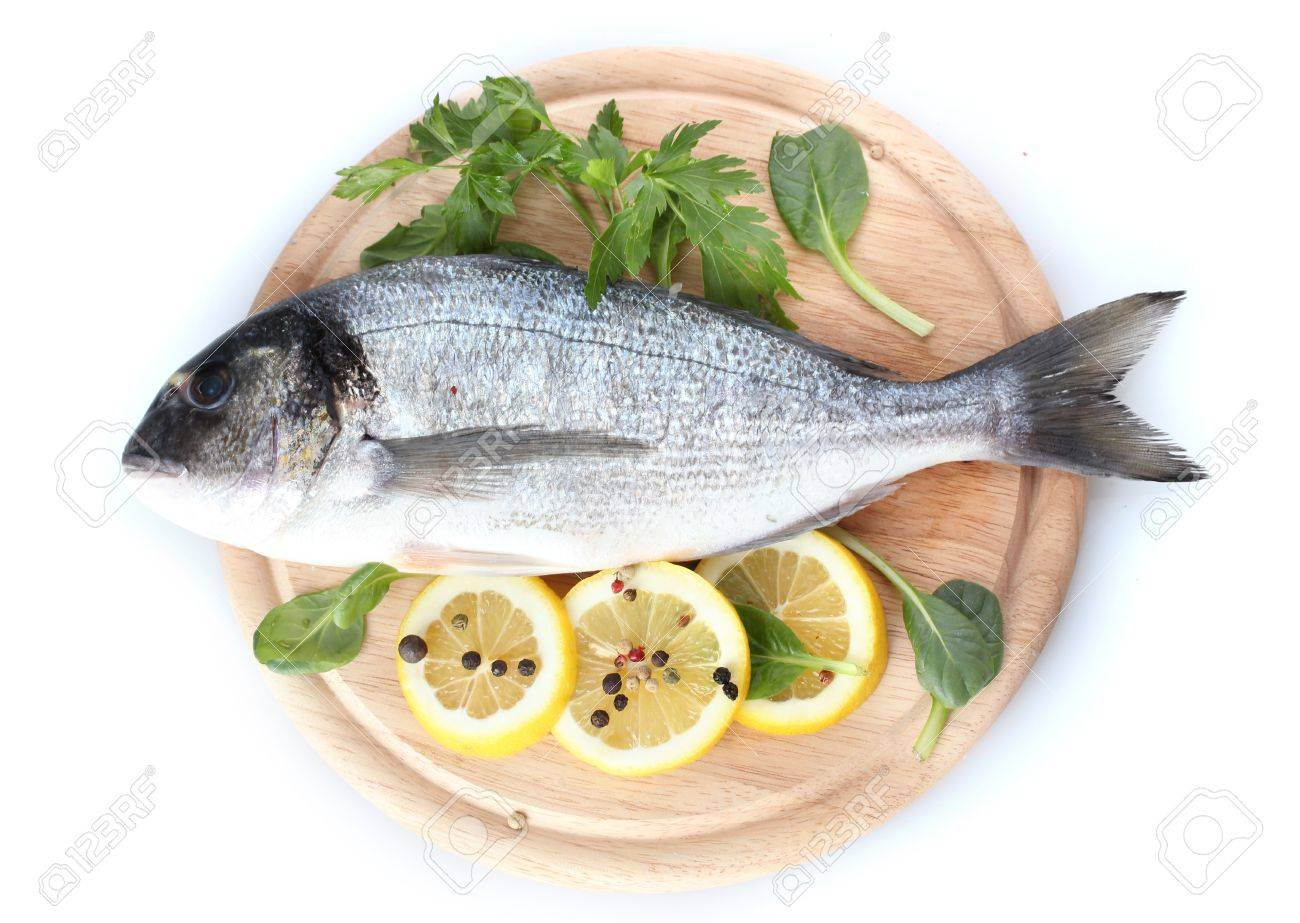 Fresh fish with lemon, parsley and spice on wooden cutting board isolated on white Stock Photo - 13356078
