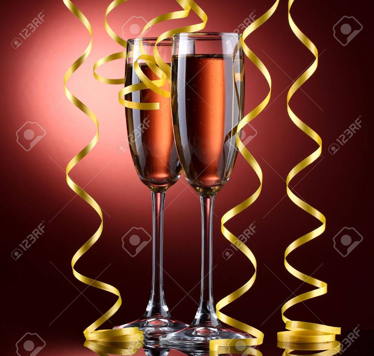 glasses of champagne and streamer on red background Stock Photo - 13355963