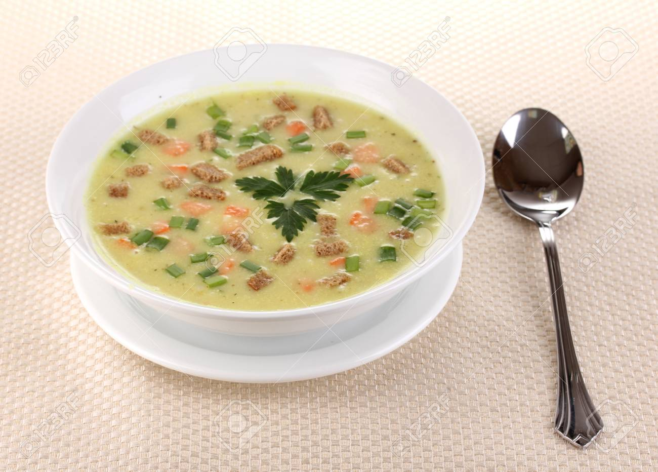 Tasty soup on beige tablecloth isolated on white Stock Photo - 13438124