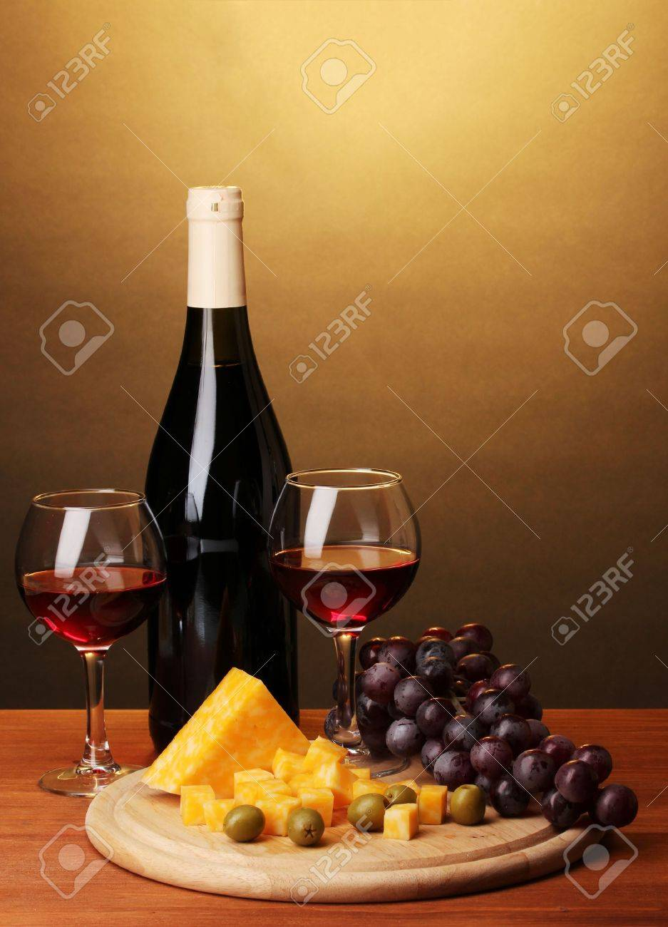 Bottle of great wine with wineglasses and cheese on wooden table on brown background Stock Photo - 13438028