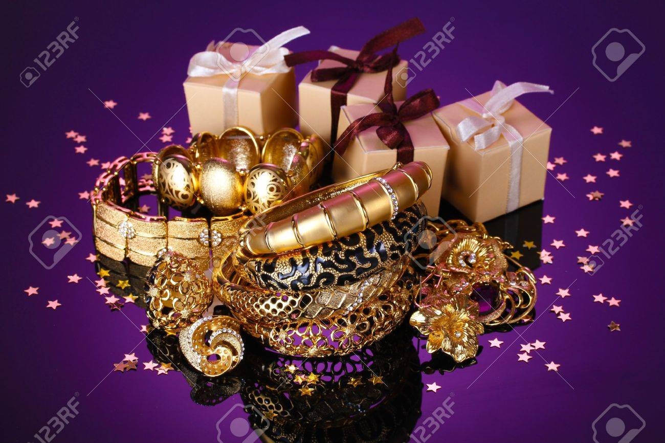 Beautiful golden jewelry and gifts on purple background Stock Photo - 13689185