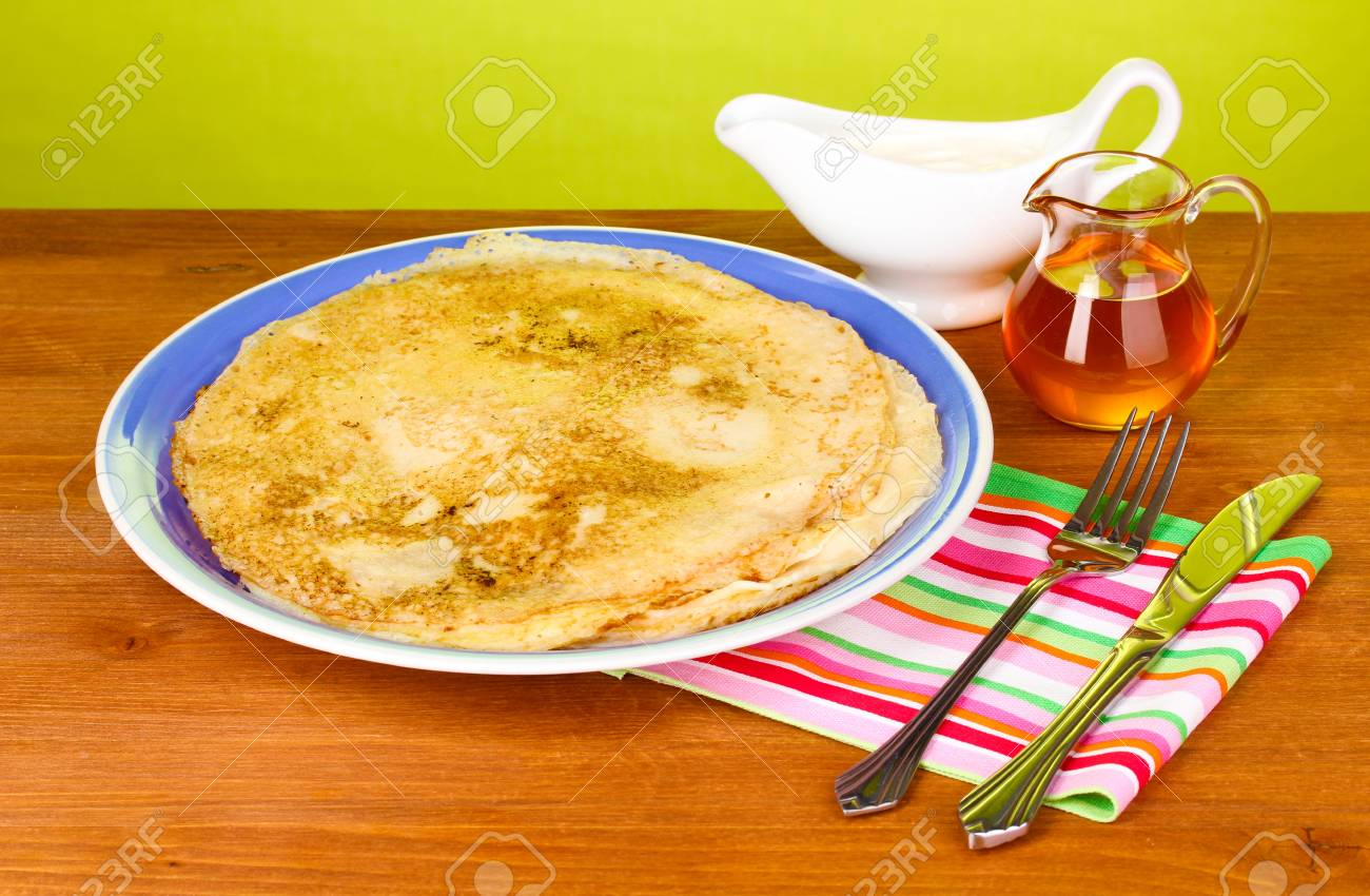 Stack of tasty pancakes on wooden table on green background Stock Photo - 13835426