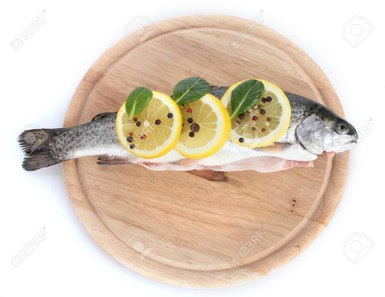 Fresh fish with lemon, parsley and pepper on wooden cutting board isolated on white Stock Photo - 13870754