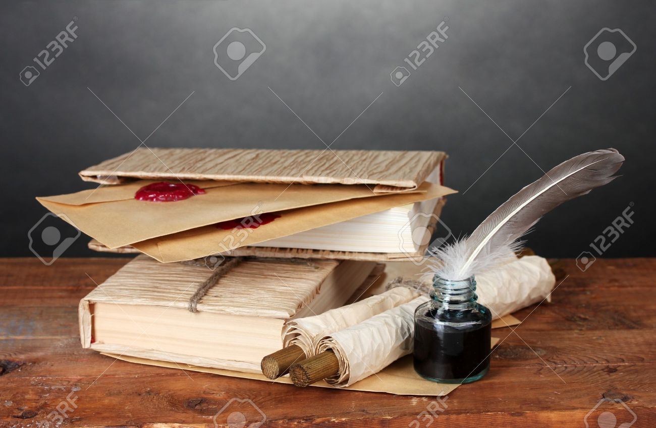 old books, scrolls, feather pen and inkwell on wooden table on grey background Stock Photo - 14135107