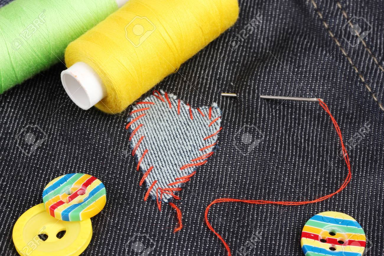 Heart-shaped patch on jeans with threads and buttons closeup Stock Photo - 14042636