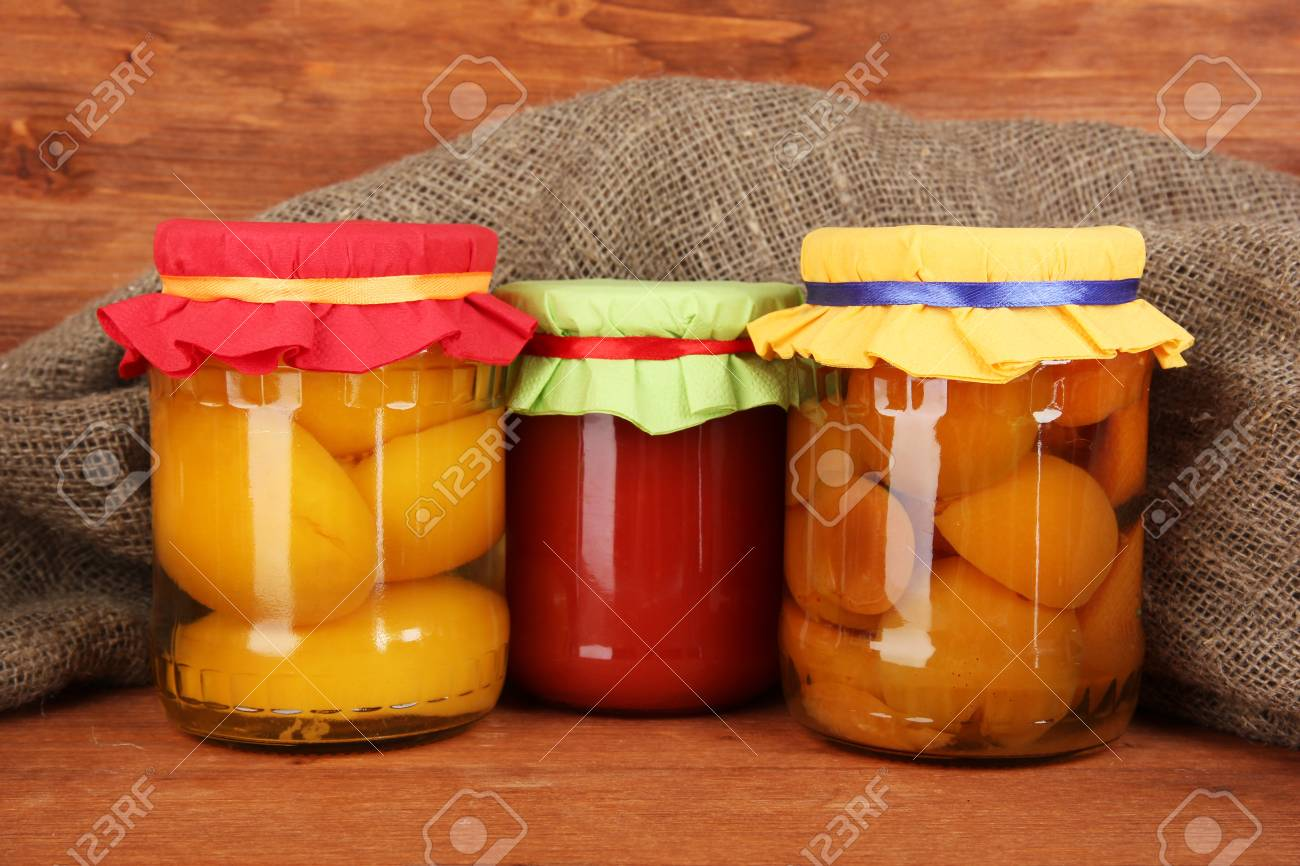 Jars with canned fruit on wooden background close-up Stock Photo - 14159437