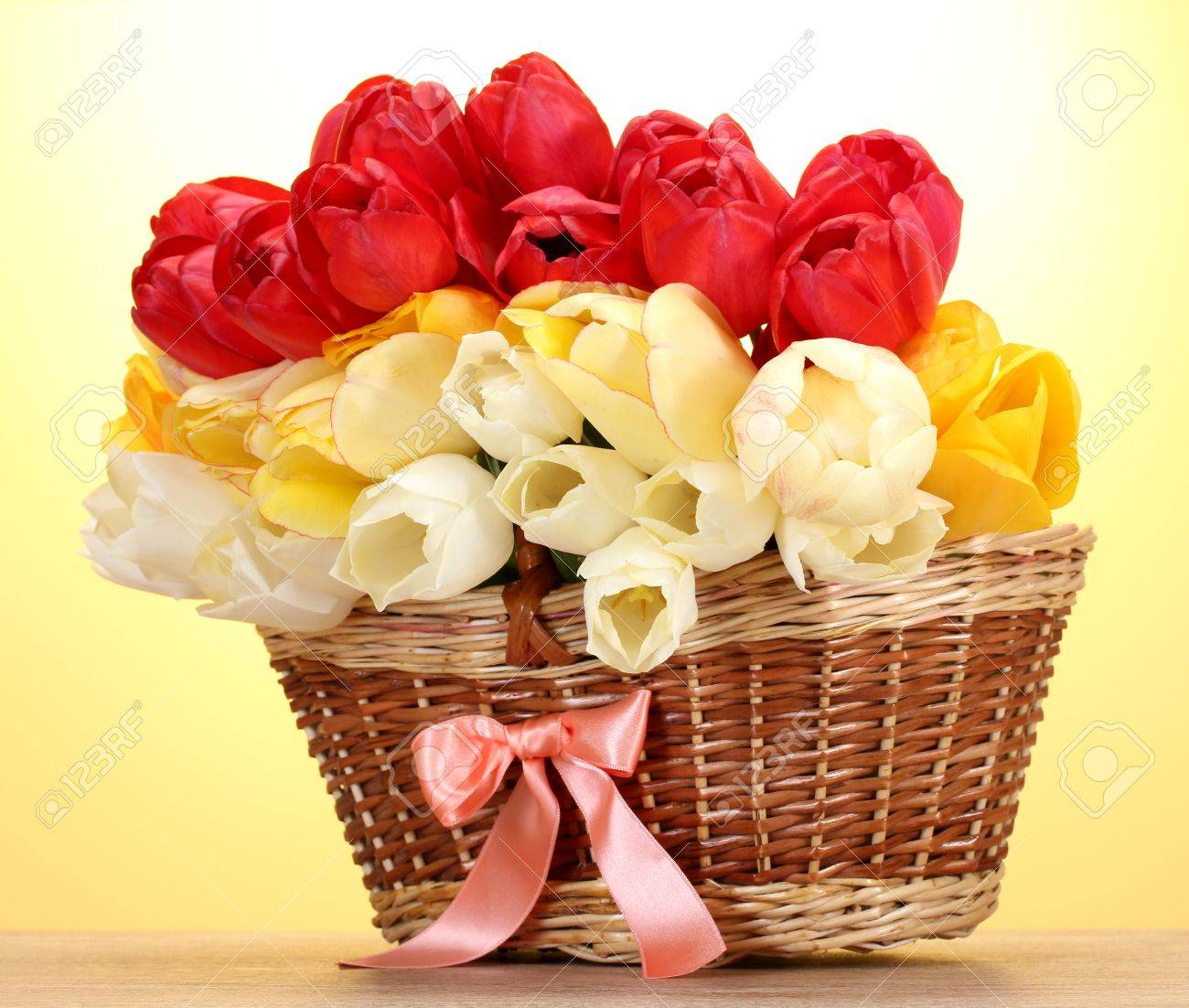 Bunch of flowers stock photos royalty free bunch of flowers images beautiful tulips in basket on wooden table on yellow background izmirmasajfo Image collections