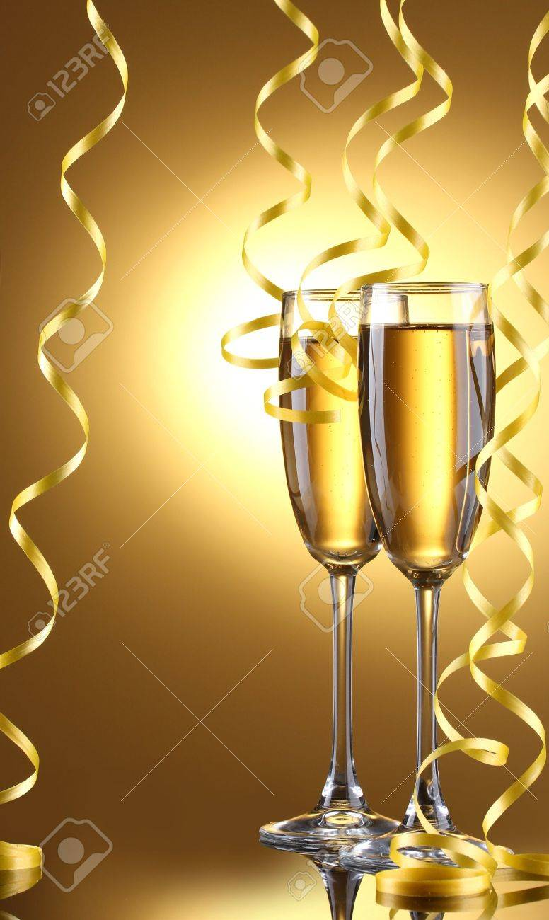glasses of champagne and streamer on yellow background Stock Photo - 14528531