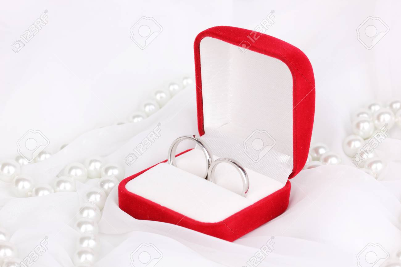 Wedding Rings In Red Box On White Cloth Background Stock Photo