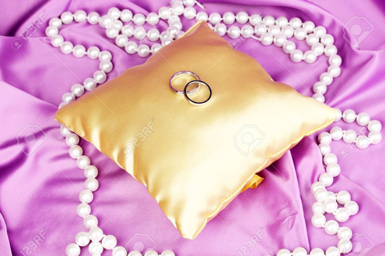 Wedding Rings On Satin Pillow On Purple Cloth Background Stock Photo ...