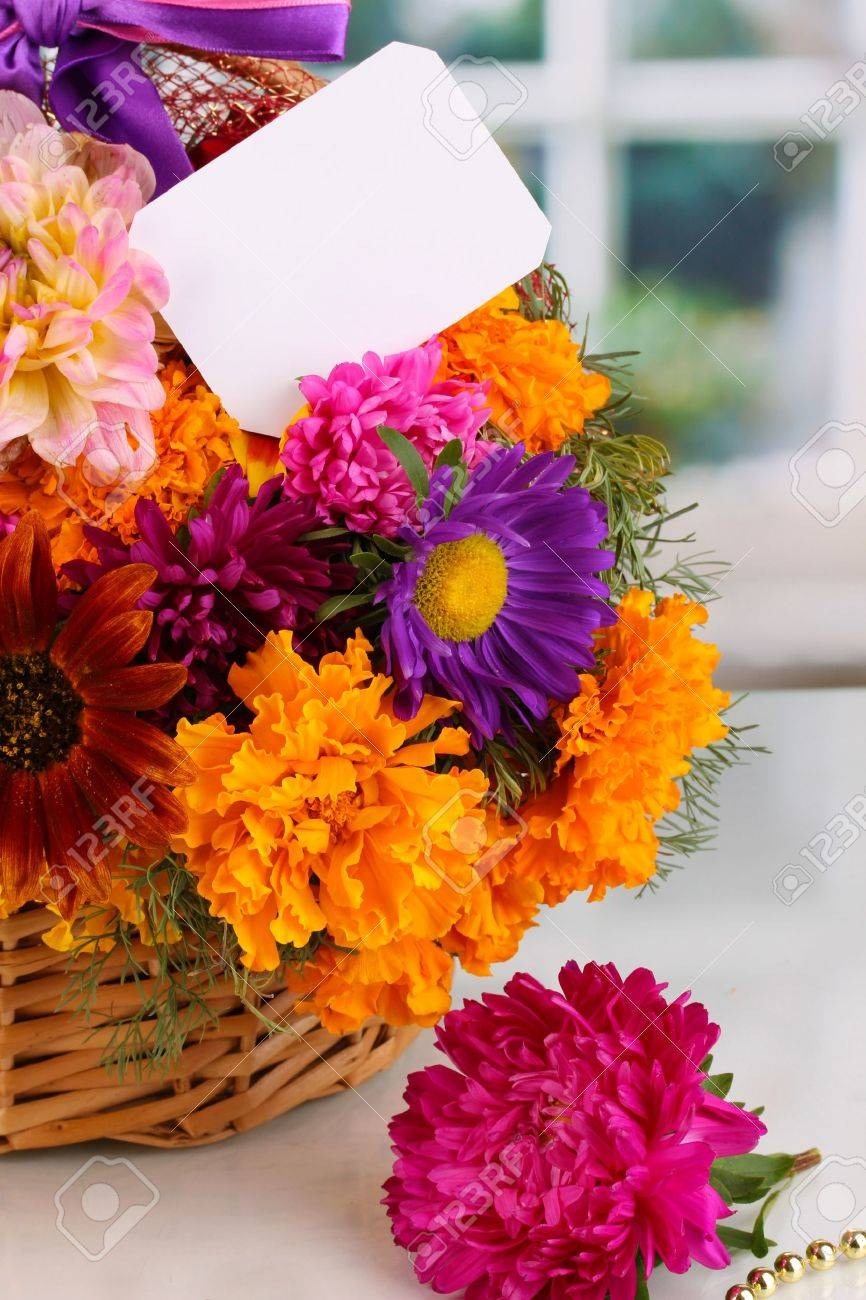 Beautiful bouquet of bright flowers in basket with paper note close-up on white table on window background Stock Photo - 15592783