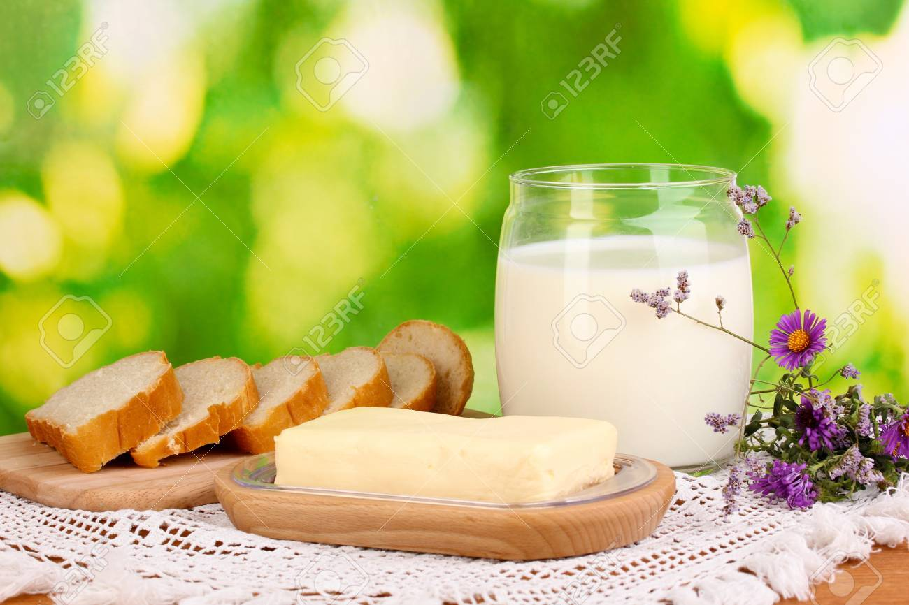 Butter on wooden holder surrounded by bread and milk on natural background Stock Photo - 15609452