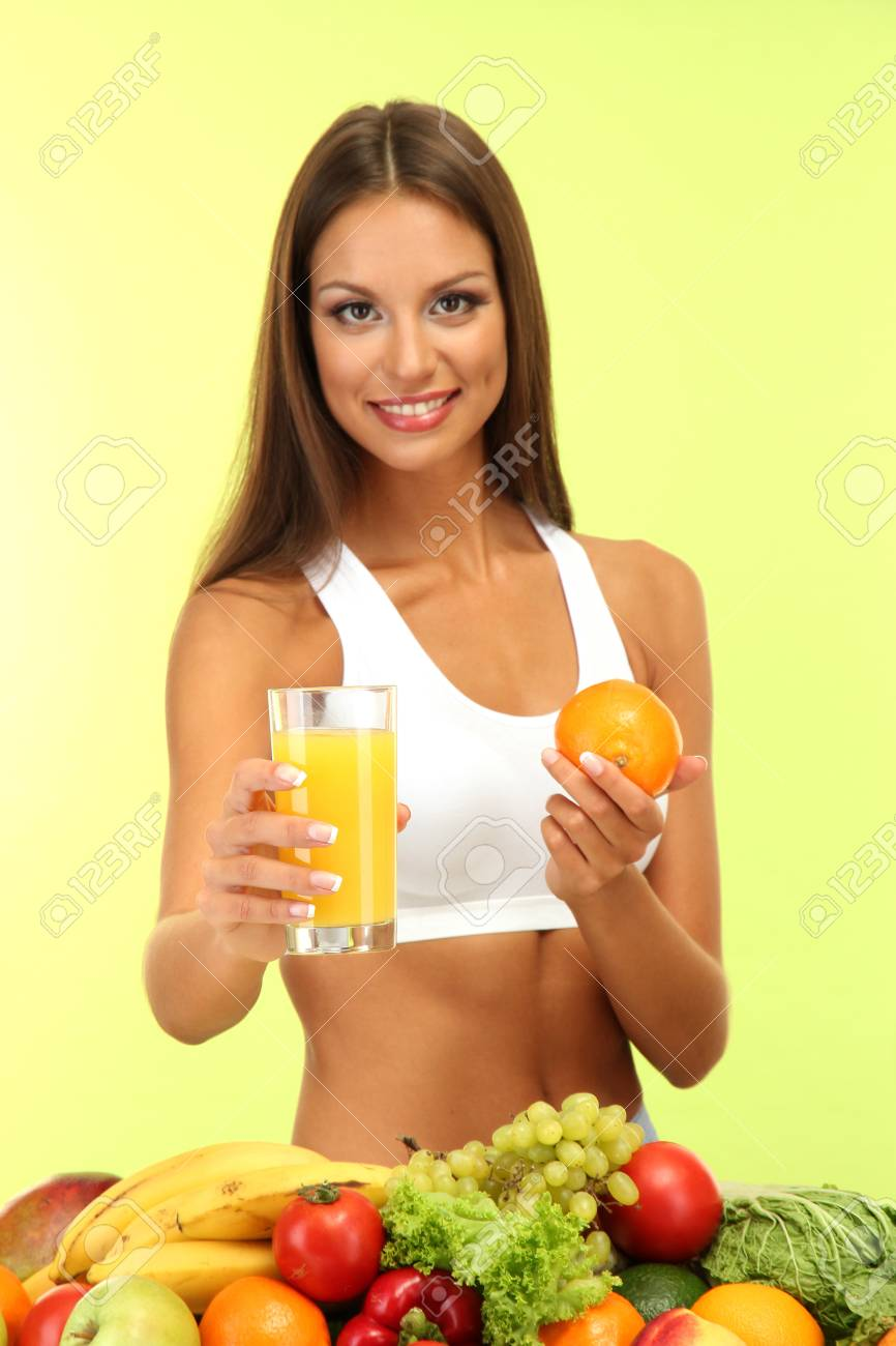 beautiful young woman with fruits and vegetables and glass of juice, on green background Stock Photo - 15833633