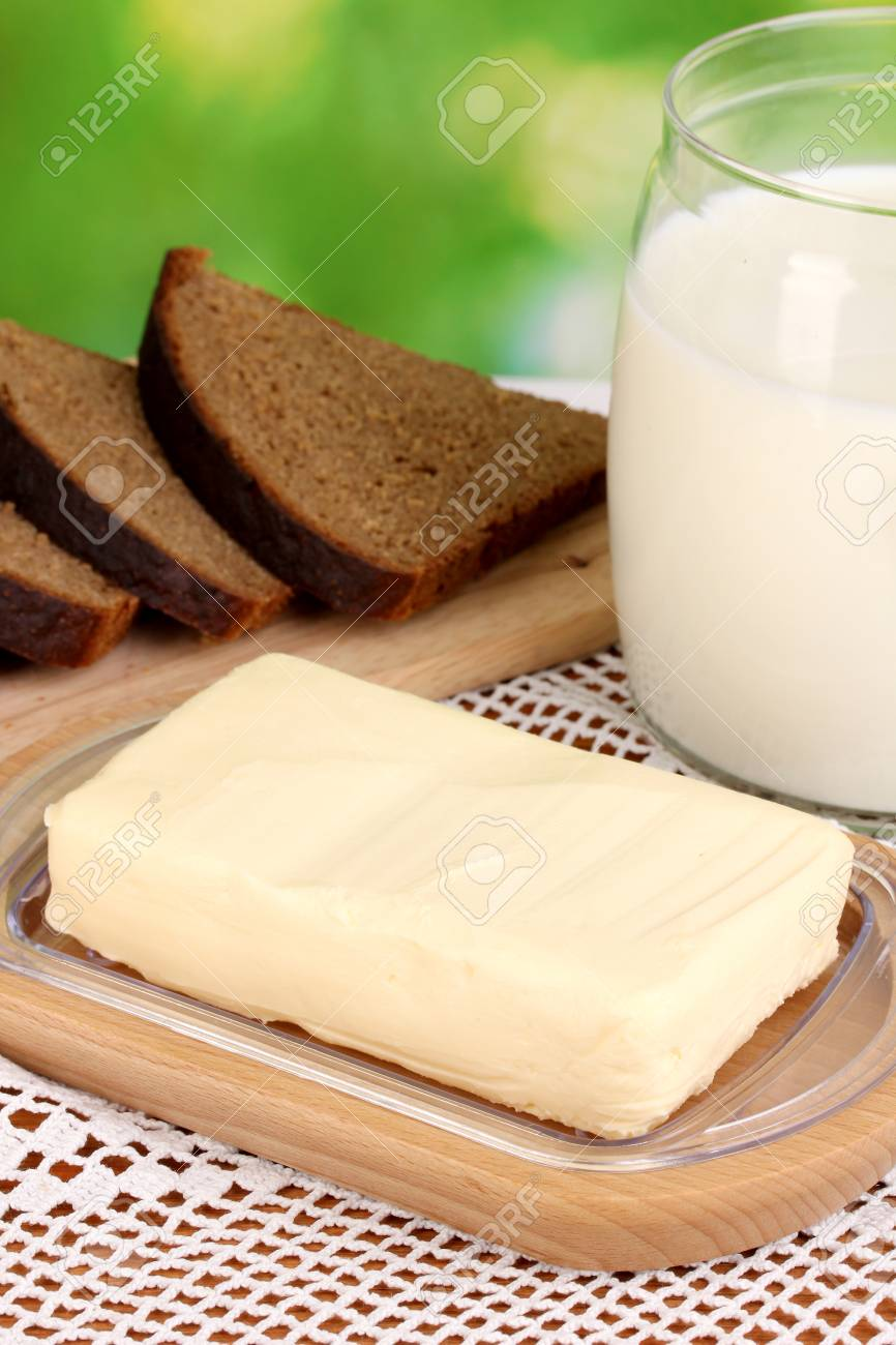 Butter on wooden holder surrounded by bread and milk on natural background close-up Stock Photo - 15765270