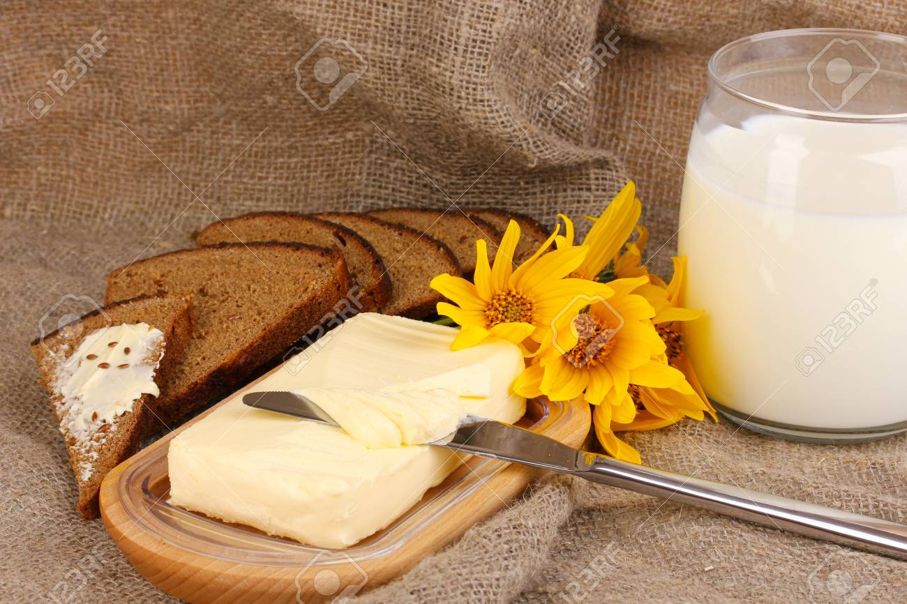 Butter on wooden holder surrounded by bread and milk on sacking background Stock Photo - 15773791