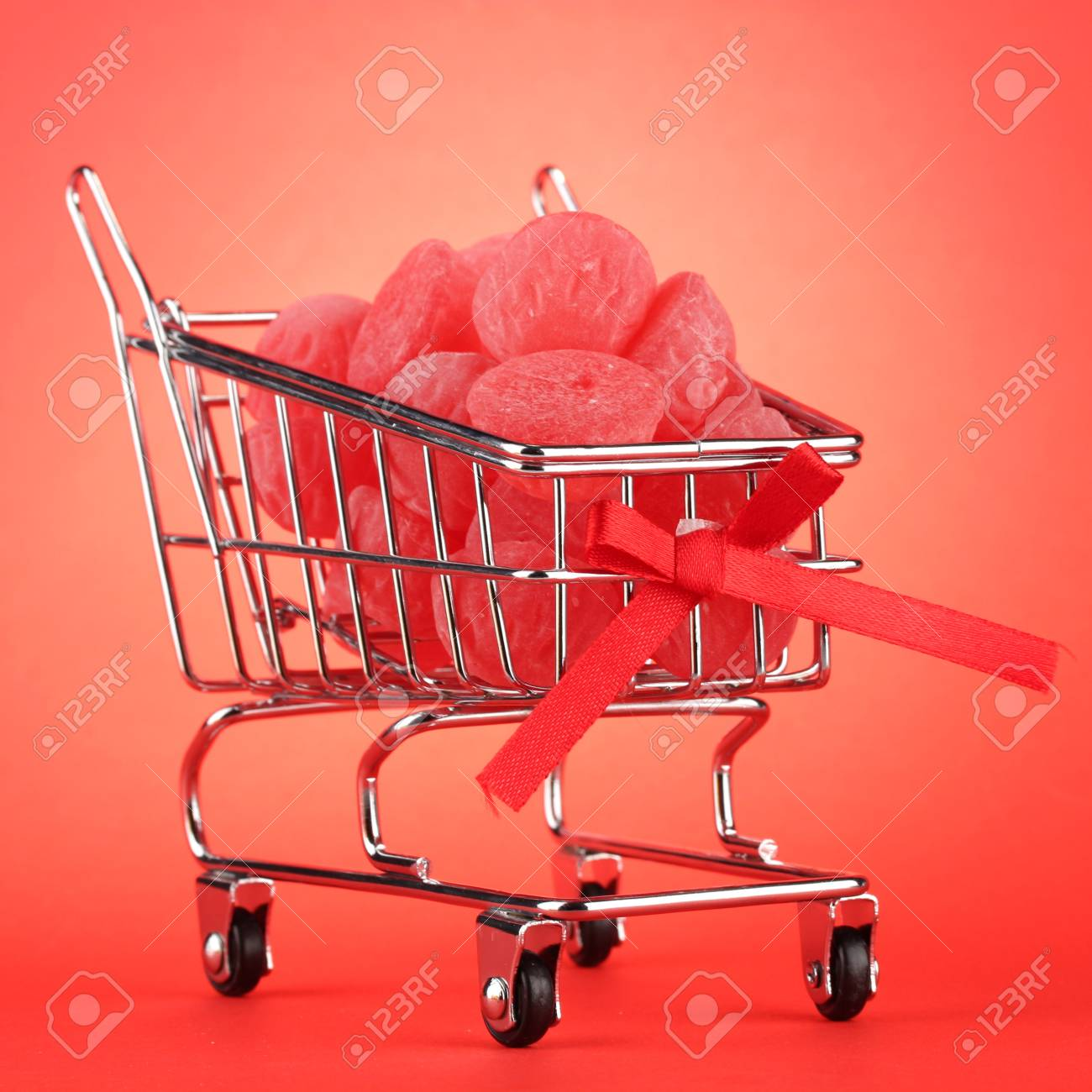 shopping trolley with jelly candies, on red background Stock Photo - 15898229