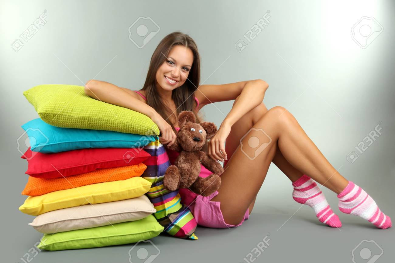 beautiful young girl and fluffy bear with pillows on grey background Stock Photo - 16346576
