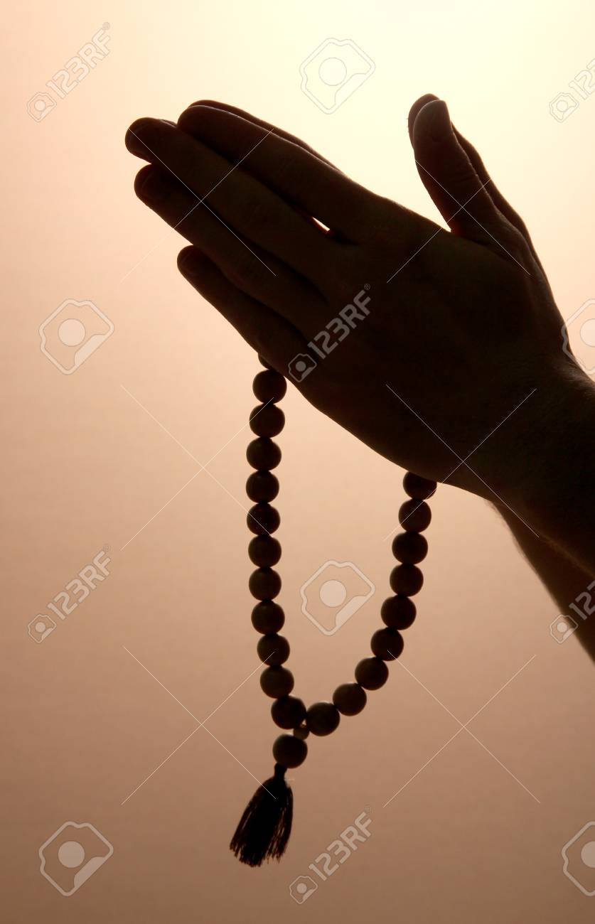 male hands with rosary, on brown background Stock Photo - 15964687