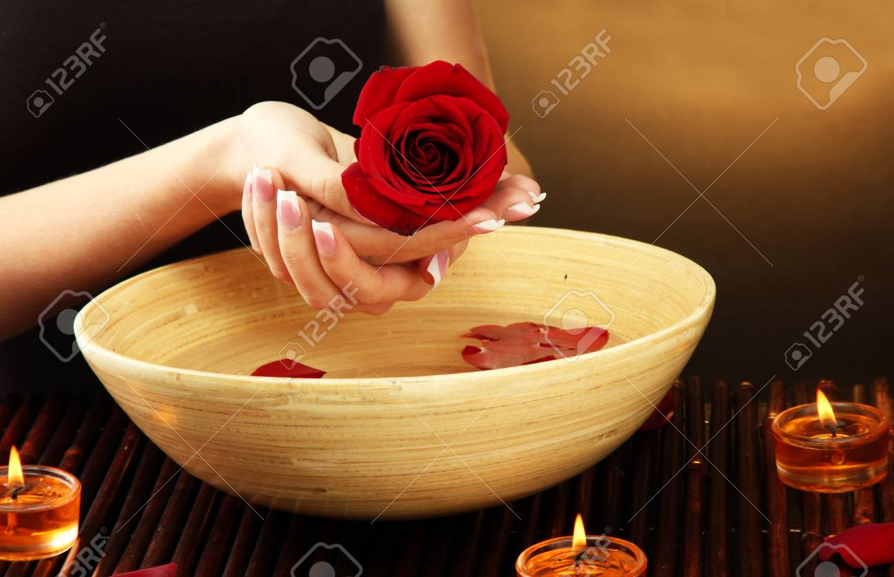 woman hands with wooden bowl of water with petals, on brown background Stock Photo - 16036818