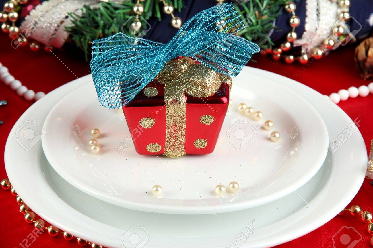 Small Christmas gift on plate on serving Christmas table background..