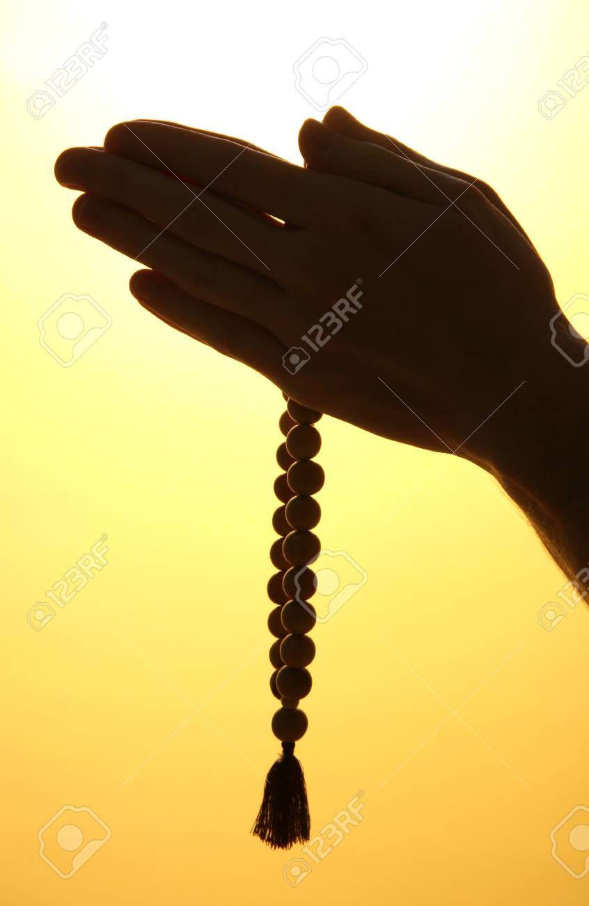 male hands with rosary, on yellow background Stock Photo - 16107338