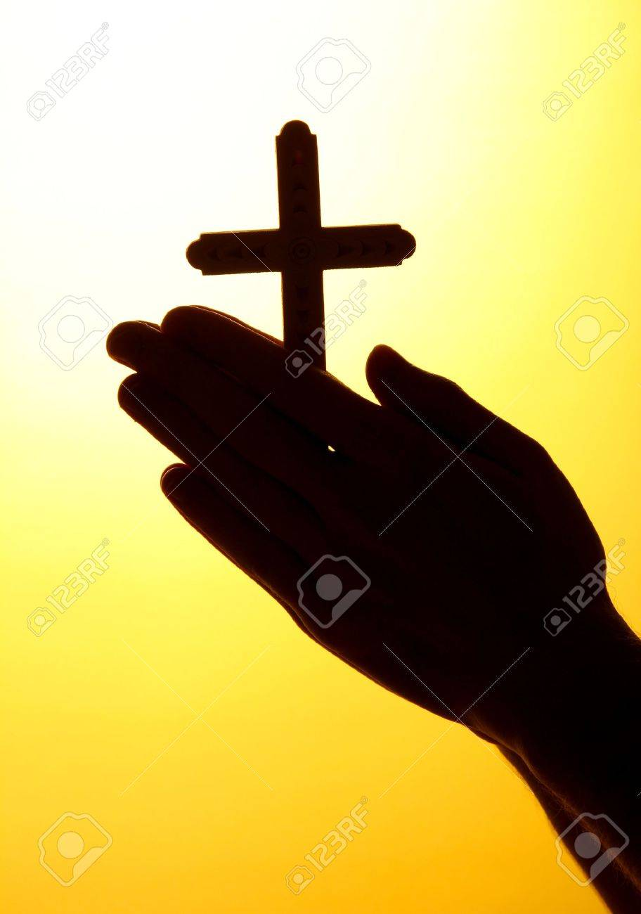 man hands with crucifix, on yellow background Stock Photo - 16218360