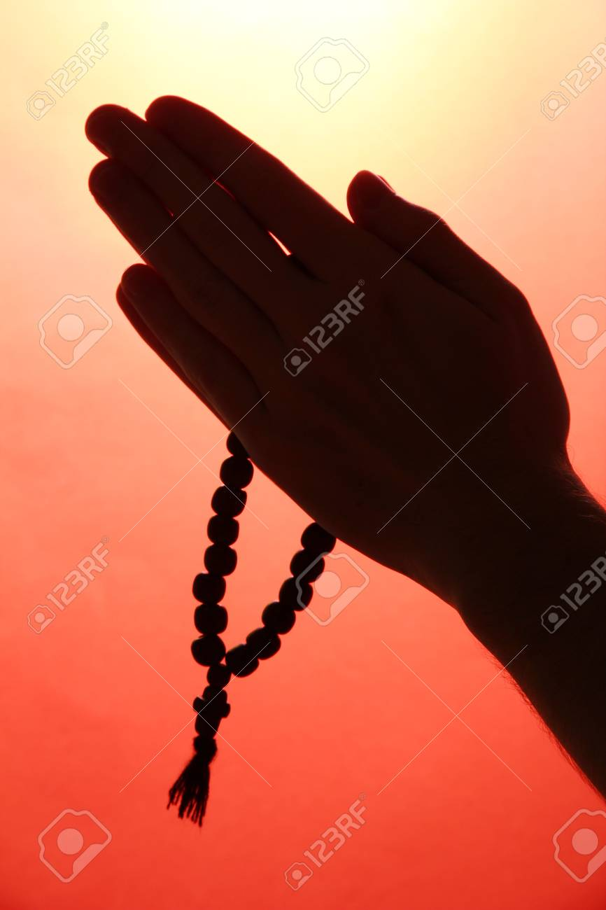 male hands with rosary, on red background Stock Photo - 16318421