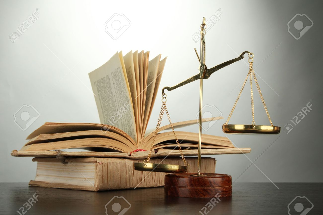Gold scales of justice and books on grey background Stock Photo - 16467530