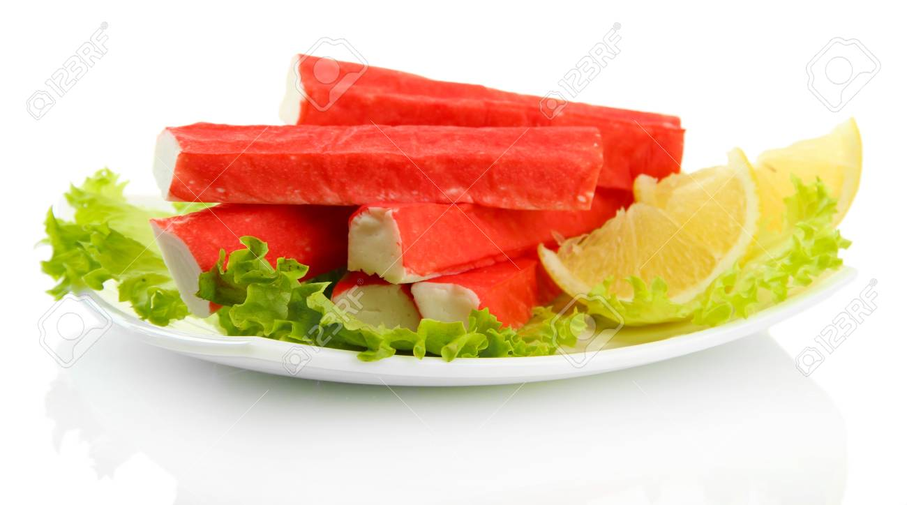 Crab sticks with lettuce leaves and lemon on plate isolated on white Stock Photo - 16645151