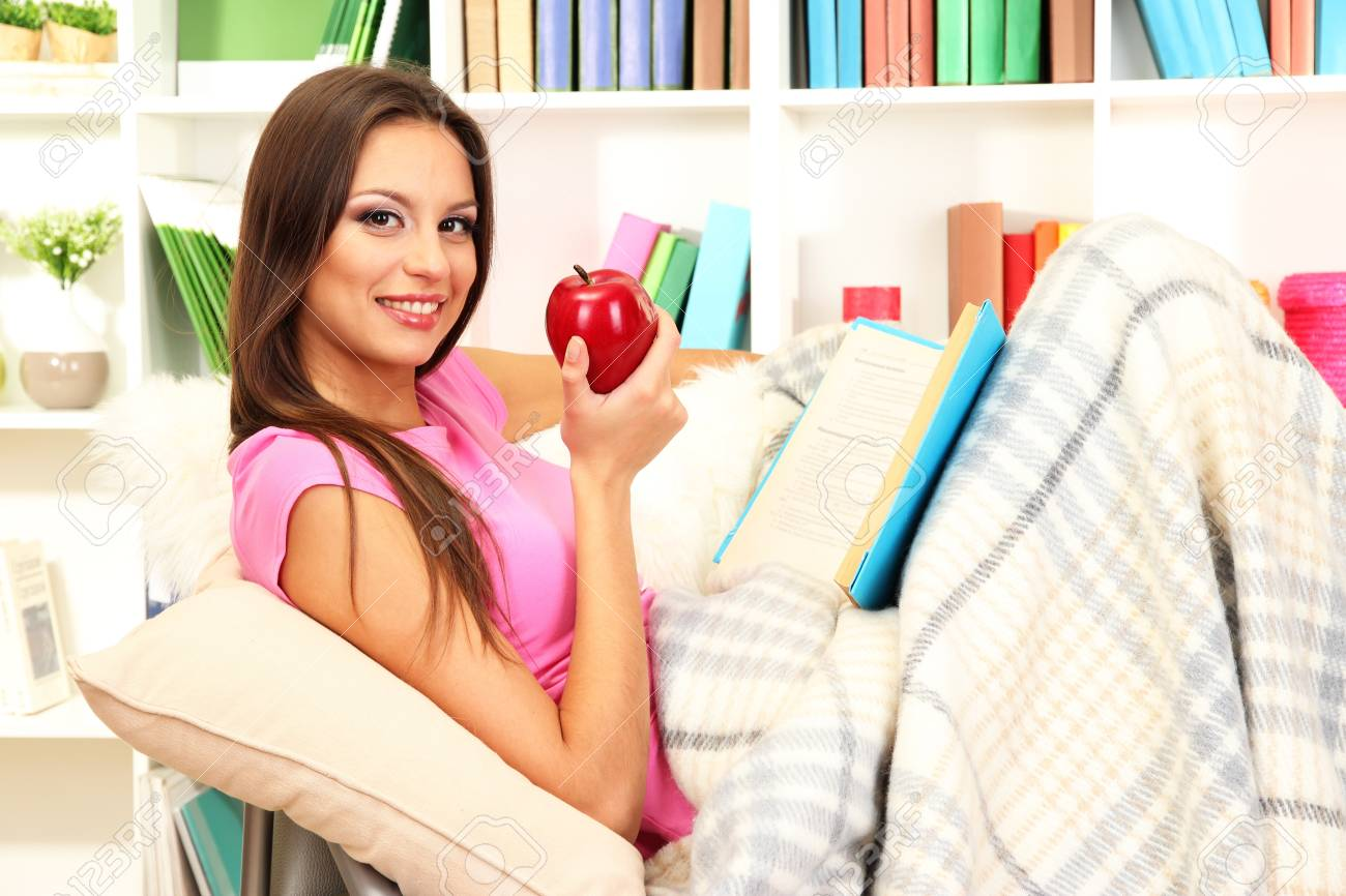 Portrait of female eating apple and reading book while lying on couch Stock Photo - 17281795