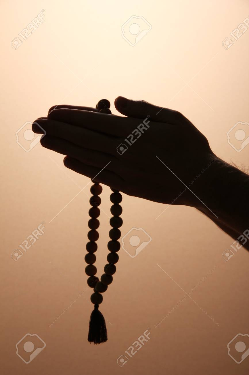 male hands with rosary, on brown background Stock Photo - 16765129