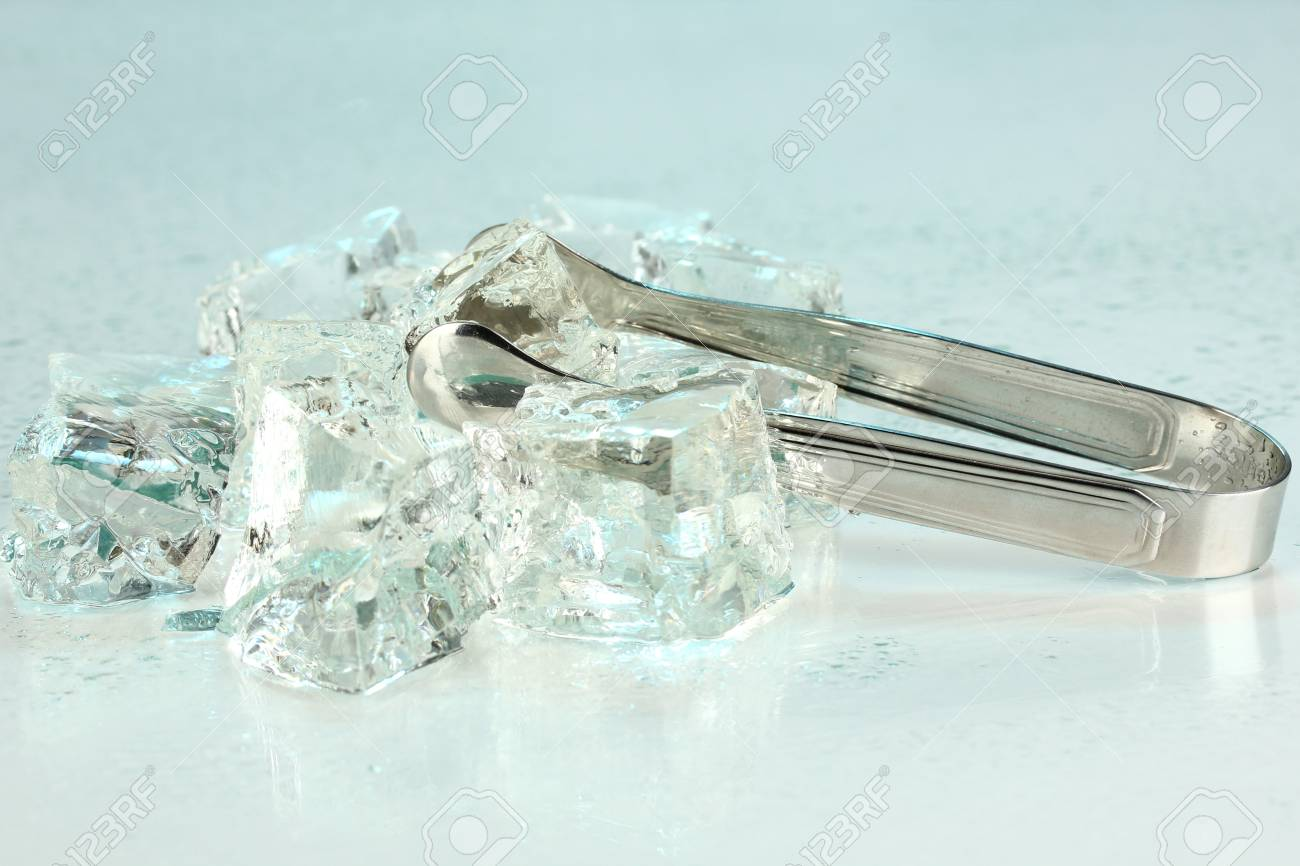 Ice cubes with tongs on light blue background Stock Photo - 16859518