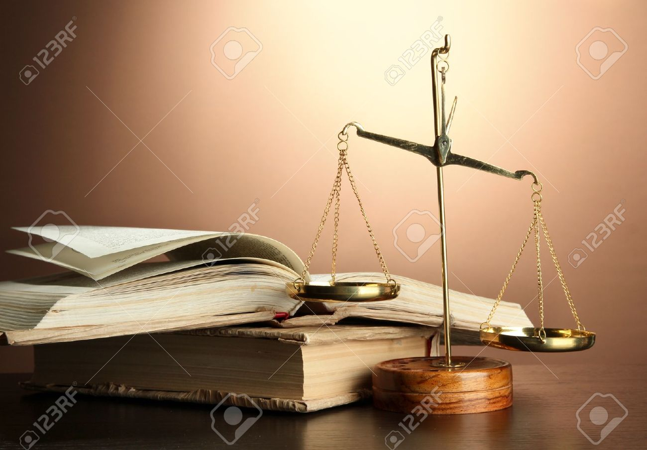 Gold scales of justice and books on brown background Standard-Bild - 16860858
