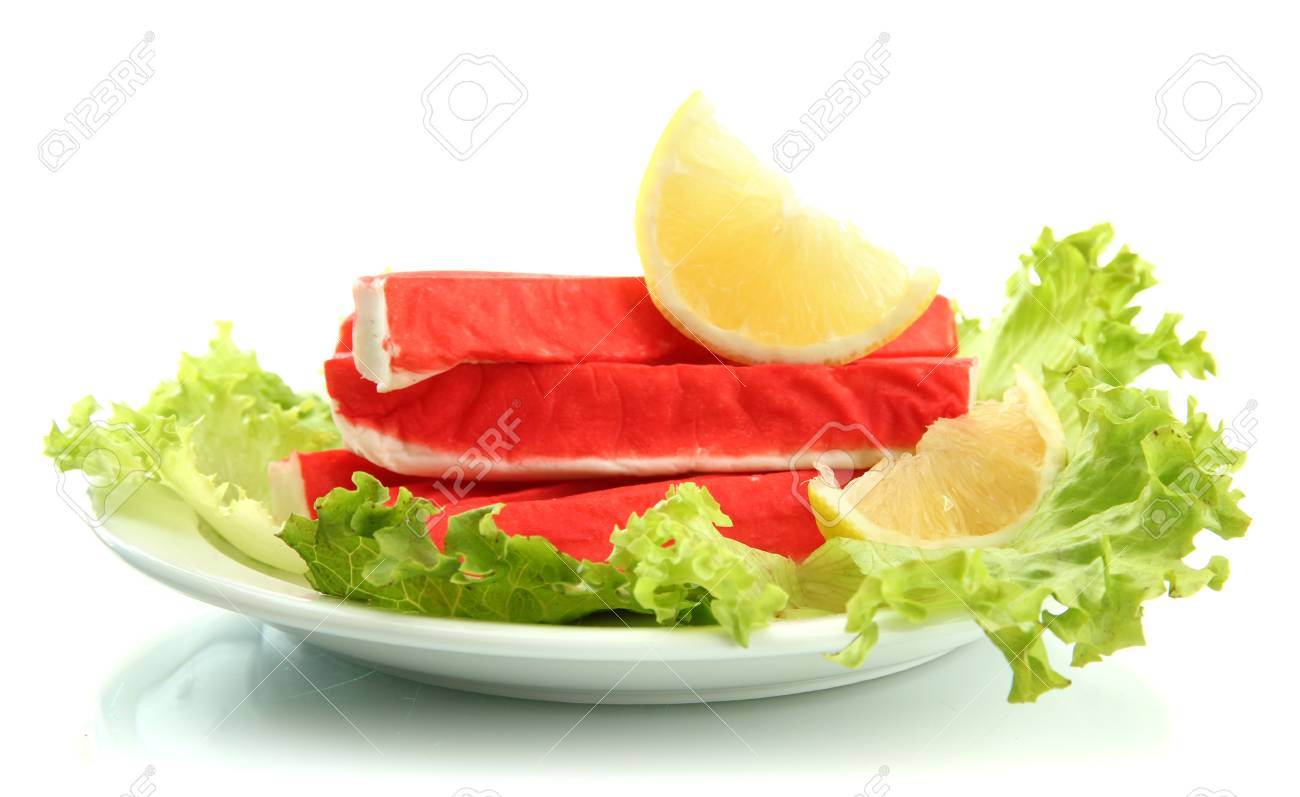 Crab sticks with lettuce leaves and lemon on plate isolated on white Stock Photo - 16860783