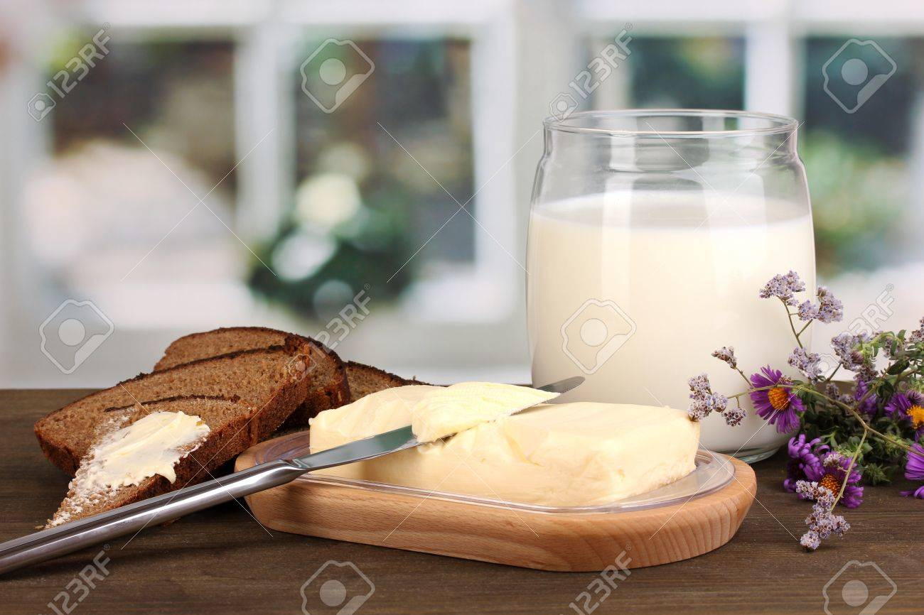 Butter on wooden holder surrounded by bread and milk on wooden table on window background Stock Photo - 16895227