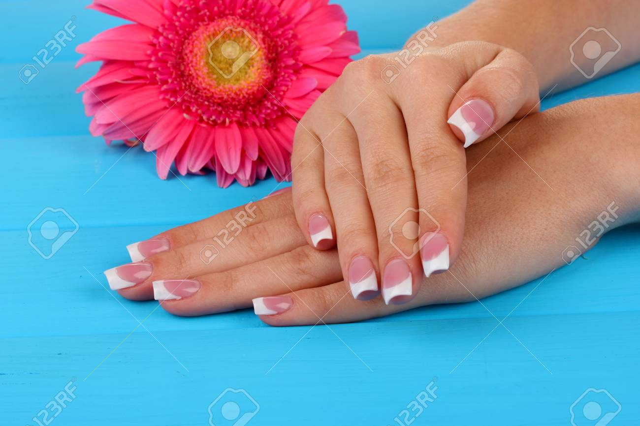 Woman hands with french manicure and flower on blue wooden background Stock Photo - 16895244