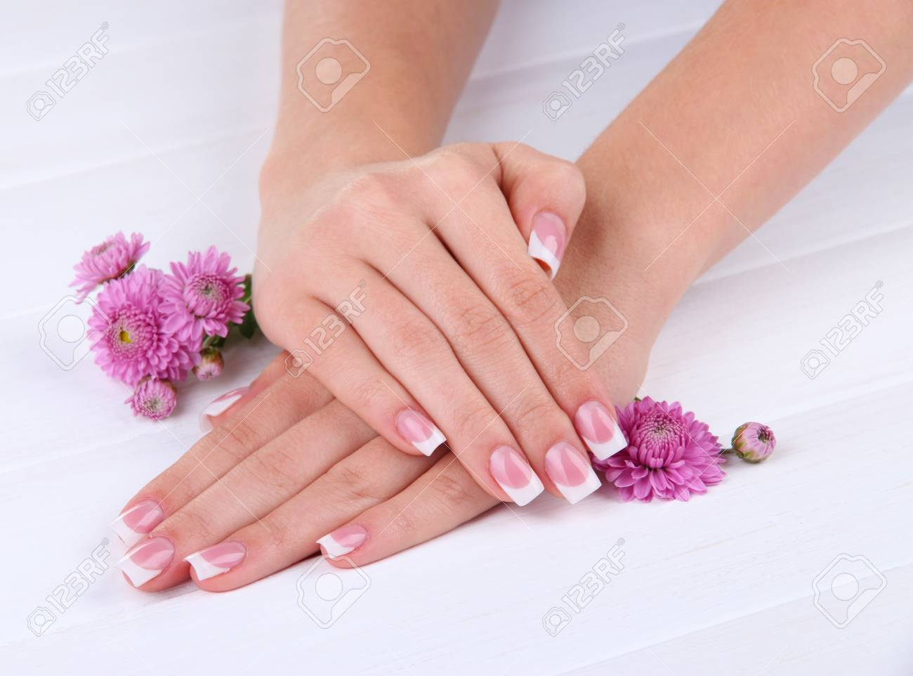 Woman hands with french manicure and flowers on white wooden background Stock Photo - 16895190